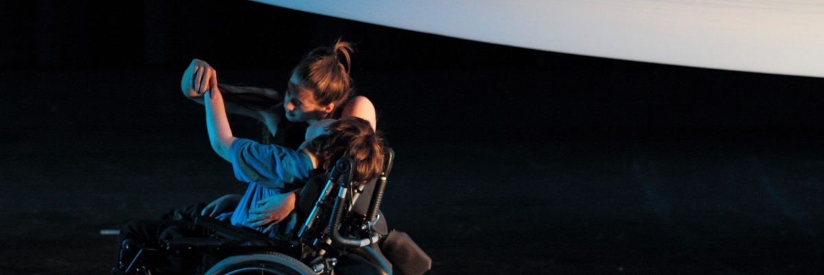 two dancers, one in a wheelchair dancing beneath a large piece of white fabric