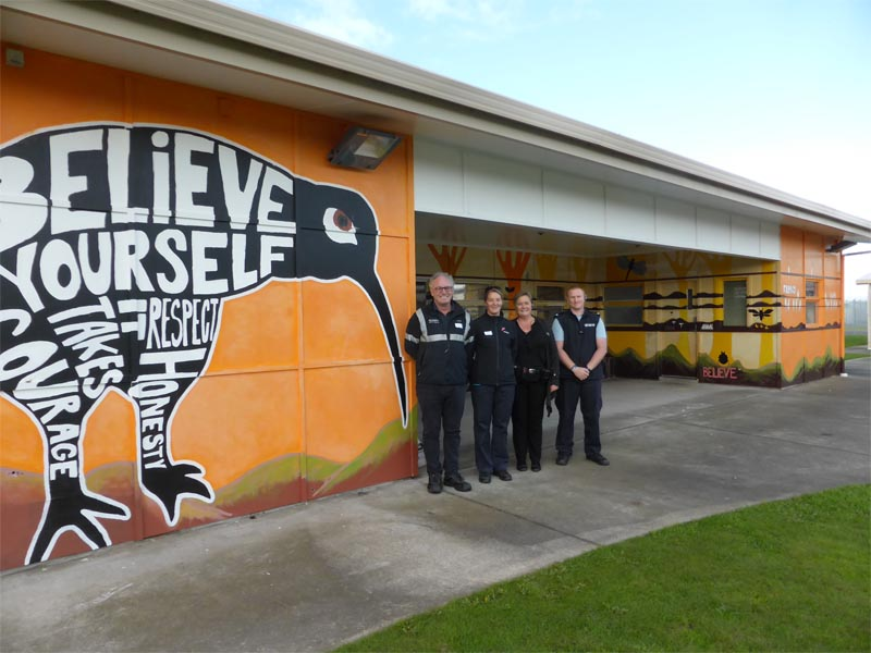 Grant Close and Alison Scarlet of Placemakers Riccarton, which donated paint towards the kiwi mural project, with Christchurch Men's Prison staff