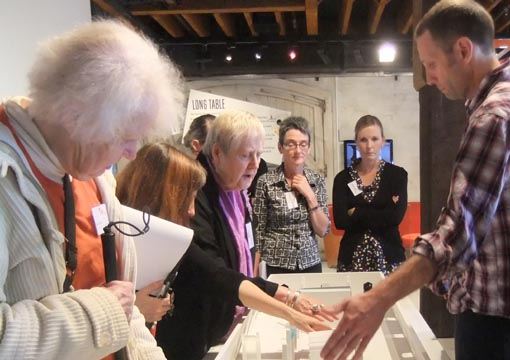 David Waller explains the tactile scale model  of The Attic to Network members