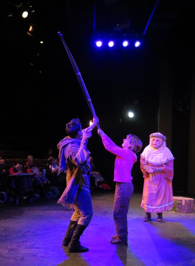 Liz on stage with Robin Hood's bow and arrows