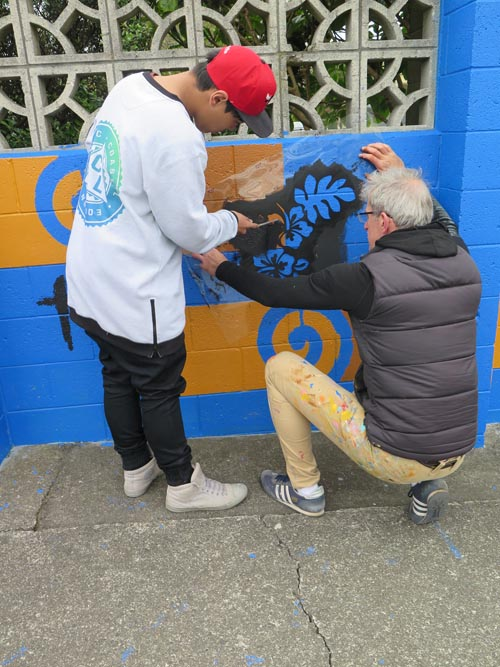 Chris Barrand works with a student on a mural in Cannons Creek
