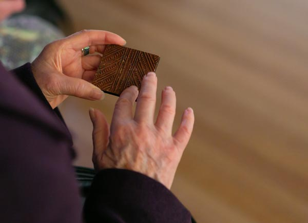 A visitor touches a small square wood panel Photo: Jo Moore, Te Papa