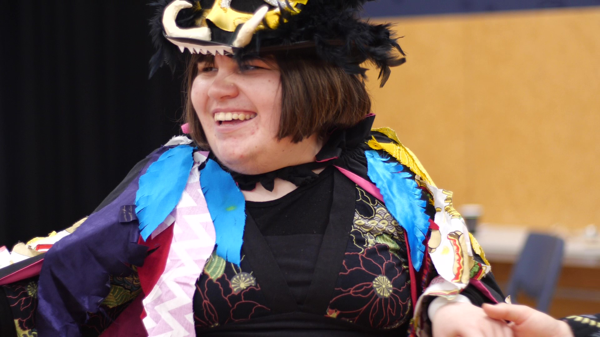 A close up of Maggie Rose Paine showing her Mag Bird Wearable Arts piece at the Disability Pride Week celebration at Te Whaea – National Dance and Drama Centre, Wellington, December 2018. A Mag bird is a cross between a Kunikuni pig and a staunch eagle. Maggie Rose is wearing a black top hat. The hat is covered in fluffy black feathers and has two cream coloured clay tusks on the front brim. She has a big smile on her face and looks like she is in her element! Her Mag Bird cloak is draped over her shoulders. It is covered in feathers made of all different sorts of patterned and colourful cloth.