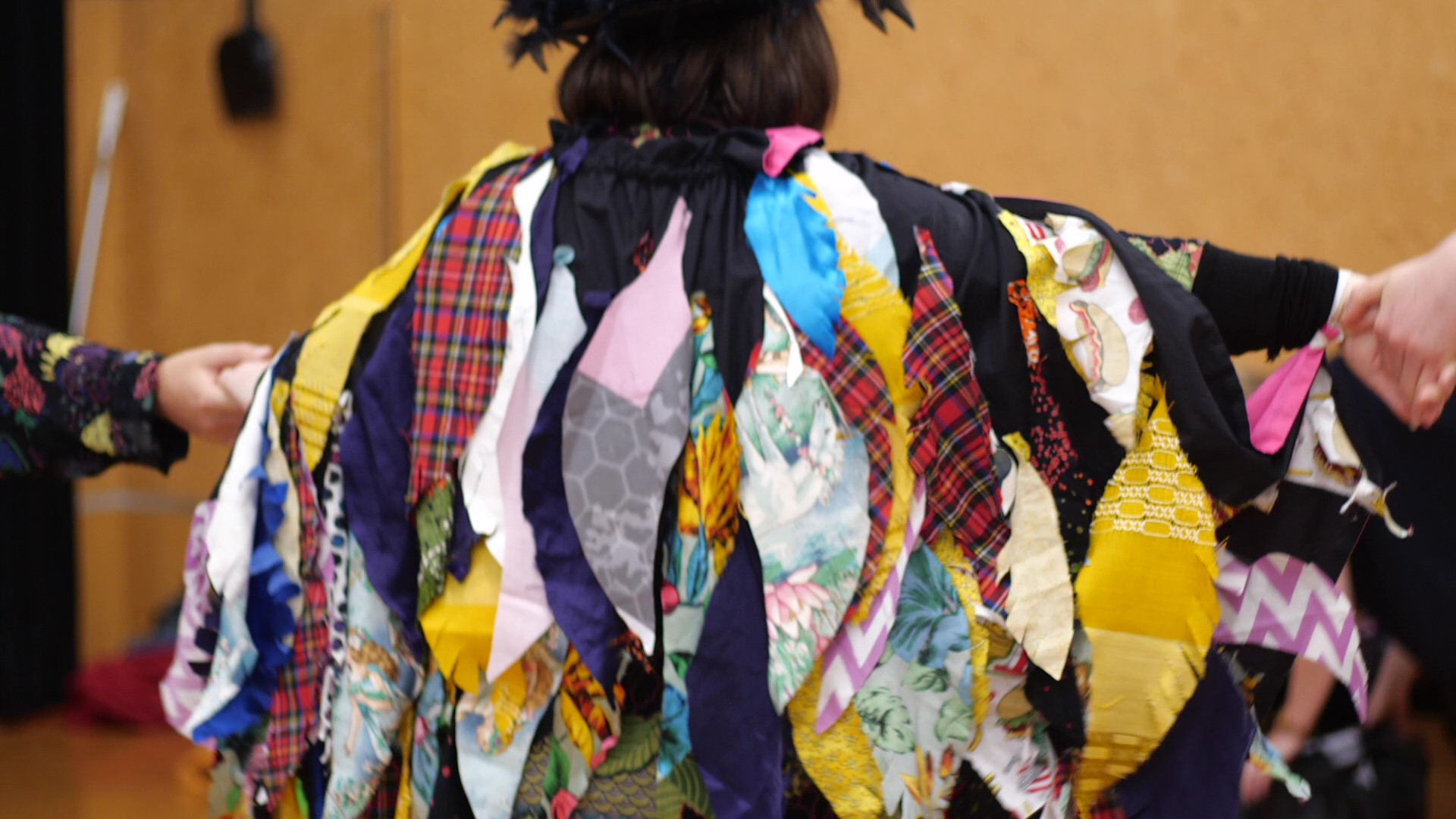 "In this image Mag Bird has her arms extended to show the back of her rainbow feather cloak and wings. She is holding hands with her team, one on each side, as she extends her wings. Her cloak is covered in dozens of feathers that were cut from cloth and sewn onto a cape. The feathers are layered and hanging down. There are lots of different patterns and bright colours. The tartan feathers are Maggie's favourite. Maggie describes the Mag Bird as having ""rainbow feathers""."