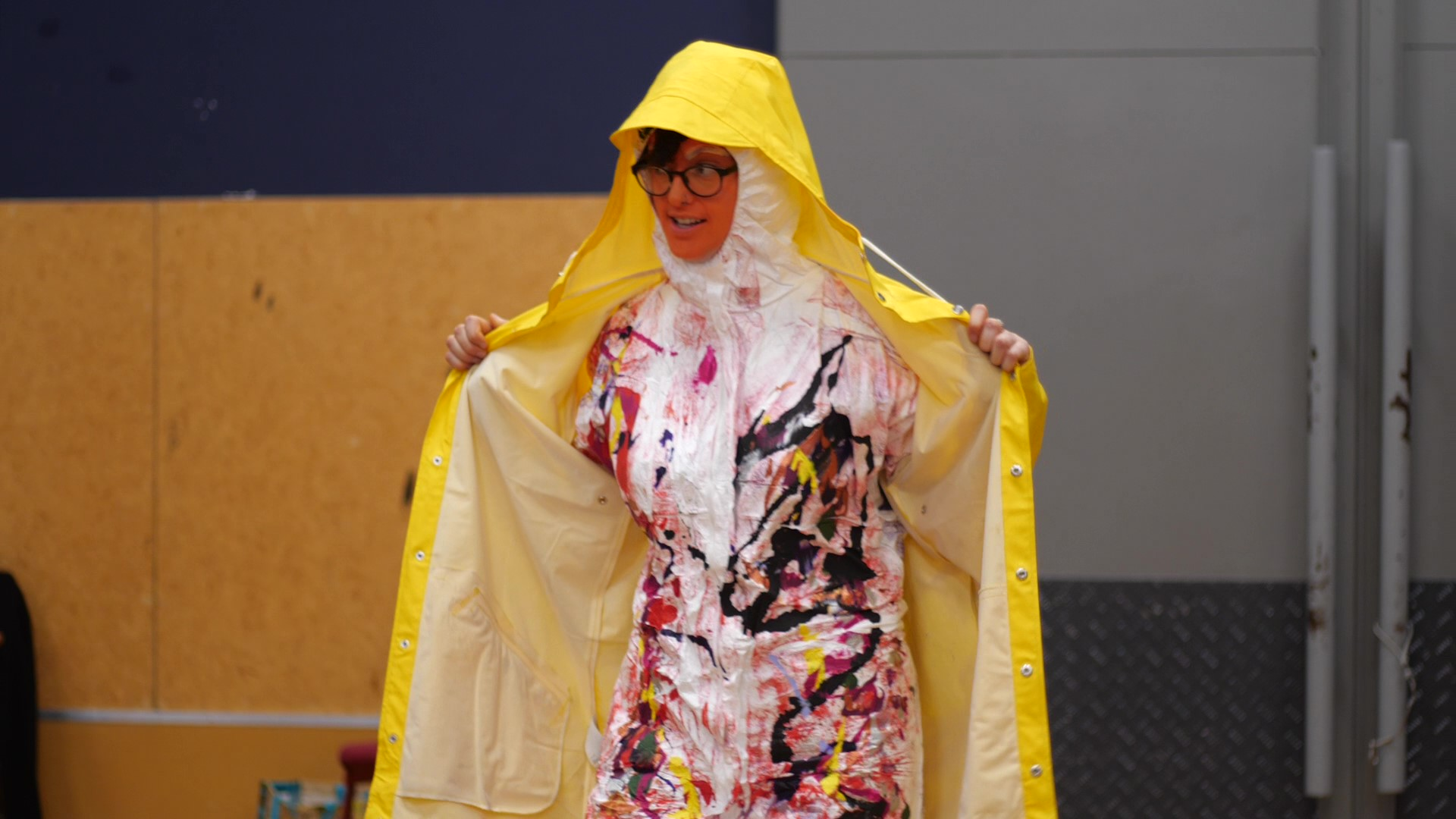 This image is of Sylvie McCreanor modelling Paul Holme's wearable arts piece, a Disabled Oompah Loompah. Her face is painted bright orange, she is smiling and looking to the audience at her side. She is wearing black rimmed eye glasses. Sylvie is wearing a bright yellow raincoat over brightly spray painted white paper overalls. The hoods for the overalls and coat are up. She is holding the raincoat wide open to expose the overalls underneath. Paul has drizzled and splattered black, yellow, orange, red, purple and pink paint down the front of the overalls. The pattern looks like a multi-coloured, braided swirling river and continues from shoulders to feet. The back of the overalls are spray painted purple and the hood has a rough stripe of green. The Ooompah Loompah music from Charlie and the Chocolate Factory is playing.