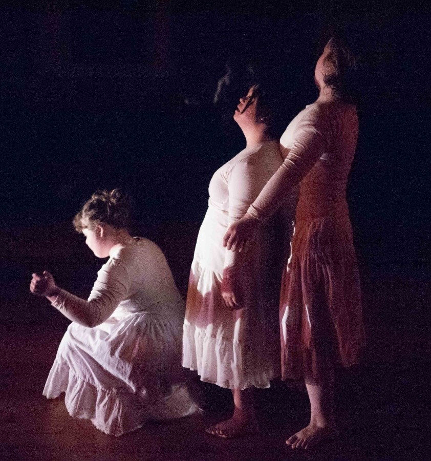 three dancers dressed in white
